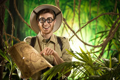 Explorer finding the right path in the jungle. Young smiling explorer in the jungle with thick glasses holding a map Stock Photography