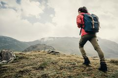 Explorer girl going up on mountain. Explorer young woman with backpack going up on mountain outdoor stock photo