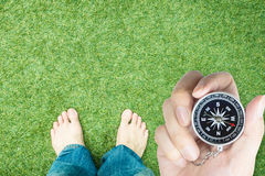 Explorer holding compass with bare feet ready to start walking. With copy space Royalty Free Stock Image