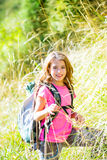 Explorer kid girl walking with backpack in grass. Explorer kid girl walking with backpack between forest grass stock image