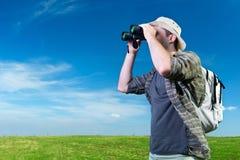 Explorer looking through binoculars. Outdoors Royalty Free Stock Photo