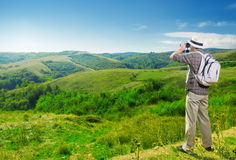 Explorer looking through binoculars outdoors. Explorer looking through binoculars nature Royalty Free Stock Images