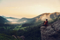 Explorer man enjoying view of sunset. Traveler young man sitting on rocky stone and enjoying view of sunset in the mountains. Toned image Royalty Free Stock Photo