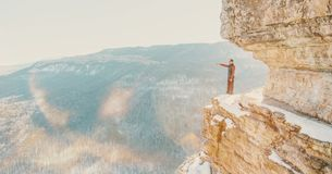 Explorer man standing on cliff Eagle shelf. Explorer young man standing on high cliff Eagle shelf and pointing into the distance in winter, Mezmay, Russia royalty free stock photos