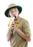 Explorer in pith helmet eating banana Royalty Free Stock Photos