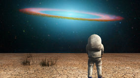 Explorer. Surrealism. Astronaut stands in arid land. Galactic disk in the starry sky. Some elements image credit NASA Royalty Free Stock Image