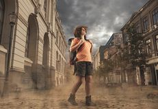 Explorer in town. Explorer woman discovers unpopulated city . Beautiful woman wearing a cowboy hat and walking in a city covered by sand Stock Photography