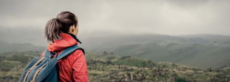 Explorer girl walking in the mountains. Explorer young woman with backpack walking in summer mountains in rainy weather royalty free stock images