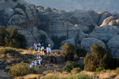 Explorers near rocks. Group of explorers near rock ridge in Dana Mountains, Jordan Stock Images