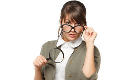 Exploring. Woman wearing old fashioned eyeglasses holding magnifying glass for better magnification over white background Stock Photography