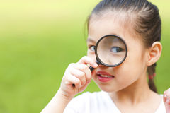 Exploring. Little girl exploring nature by magnifier Stock Photos