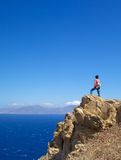 Exploring Aegean Islands. An explorer on a cliff in the Aegean islands with blue skies and sea Royalty Free Stock Photos