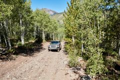 Exploring the alpine wilderness in a 4WD. With an off road vehicle climbing through mountain forests along a rough dirt road Royalty Free Stock Photos
