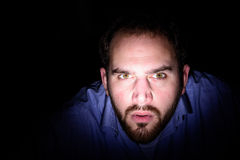 Exploring face in the dark. A man with beard looks with an inquisitive expression law in the light, concept searching in the dark Royalty Free Stock Photography