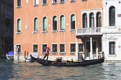 Exploring the Grand Canal. Venice, Italy - October 19, 2010 ... A gondola with two tourists aboard on the Grand Canal in Venice, Italy Royalty Free Stock Photography