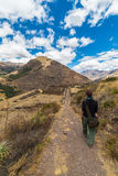 Exploring Inca Trails and Terraces of Pisac, Peru. Tourist exploring the Inca Trails leading to the ruins of Pisac, Sacred Valley, major travel destination in Stock Photo