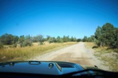 Exploring by jeep off road in Flat Tops. National Park in a first person POV looking through the windscreen at a gravel road through grassland and scrub Stock Photos