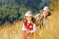 Exploring kids. Happy young safari adventure children playing outdoors in the grass with binoculars and exploring together as brother and sister stock photos
