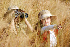 Exploring kids. Happy young safari adventure children playing outdoors in the grass with binoculars and exploring together as brother and sister royalty free stock photography