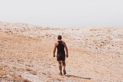 Exploring - lonely human walking in a rocky desert freedom and adventure lifestyle and sport concepts. Exploring - lonely human walking in a rocky desert royalty free stock images