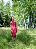Exploring Nature. A Young Woman is Wading Forest Meadow in Awe of Nature Immensity Royalty Free Stock Photography
