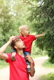 Exploring nature. Cute toddler boy siting on the shoulders of his father and touches a branch of fir tree. Parenting concept stock photography