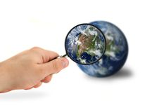 Exploring our world. Hand with magnifying glass over the globe isolated on white Royalty Free Stock Photos