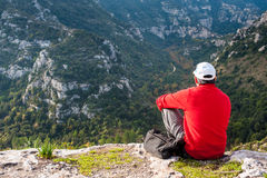 Exploring Pantalica. Hiker sitting on the rocky edge of one of Pantalica,s canyons in Sicily stock image