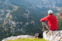 Exploring Pantalica. Hiker sitting on the rocky edge of one of Pantalica,s canyons in Sicily royalty free stock photo