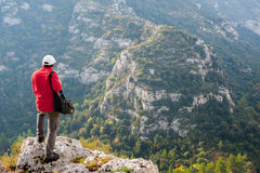 Exploring Pantalica. Hiker standng on the rocky edge of one of Pantalica,s canyons in Sicily stock photo