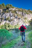 Exploring Pantalica. Hiker walking along the trails of the Anapo valley, by the rocky necropolis of Pantalica royalty free stock image
