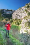 Exploring Pantalica. Hiker walking along the trails of the Anapo valley, by the rocky necropolis of Pantalica Stock Photography