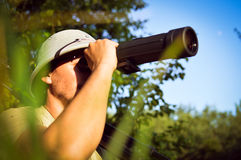 Exploring scientist in pith helmet having fun observing looking in magnification scope on summer sunny day Stock Image