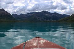 Exploring a turquoise lake in Alaska in a red boat. royalty free stock photography