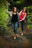 Exploring. Two pretty young country girls walking through a creek bed exploring the woods, both with long hair and smiling. Shallow depth of field Royalty Free Stock Image