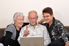 Exploring the web. Seniors man and women exploring the web Stock Photography