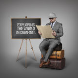 Exploring the world in comfort. text on blackboard with explorer businessman Stock Images