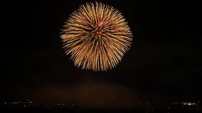 Explosão colorida clara brilhante do fogo de artifício japonês maravilhoso no céu noturno escuro sobre a cidade grande no tiro es filme
