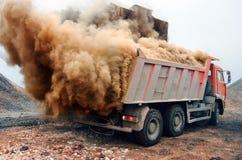 Explosão de poeira ao carregar o caminhão vermelho na mina Fotos de Stock