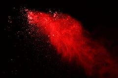Explosão do pó vermelho no fundo preto Sumário da poeira colorida splatted fotos de stock royalty free