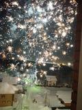Explos?es dos fogos de artif?cio atrav?s da janela aberta em uma noite do inverno fotos de stock