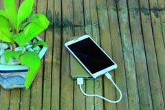 Explosión agrietada pantalla del poder de carga del teléfono En el fondo de bambú Foto de archivo