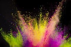 Explosi?n coloreada del polvo en fondo negro imagenes de archivo