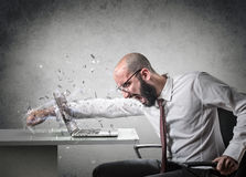 Explosion of anger. Man breaks the screen of a computer royalty free stock photo