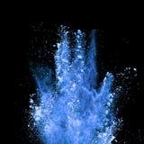 Explosion of blue powder on black background Stock Images