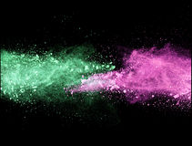 Explosion of colored powder on black background Stock Images