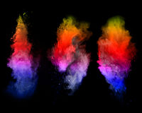Explosion of colored powders on black background Stock Photography