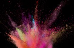 Explosion of coloured powder isolated on black background. Abstract colored background royalty free stock images