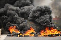 Explosion et roues brûlantes entraînant le smo foncé énorme photo libre de droits