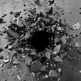 Explosion hole in concrete cracked wall. Industrial background Royalty Free Stock Images